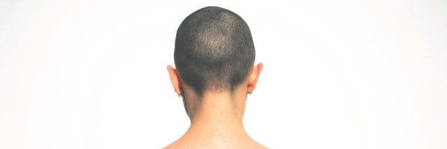 Person with shaved head, viewed from the back.