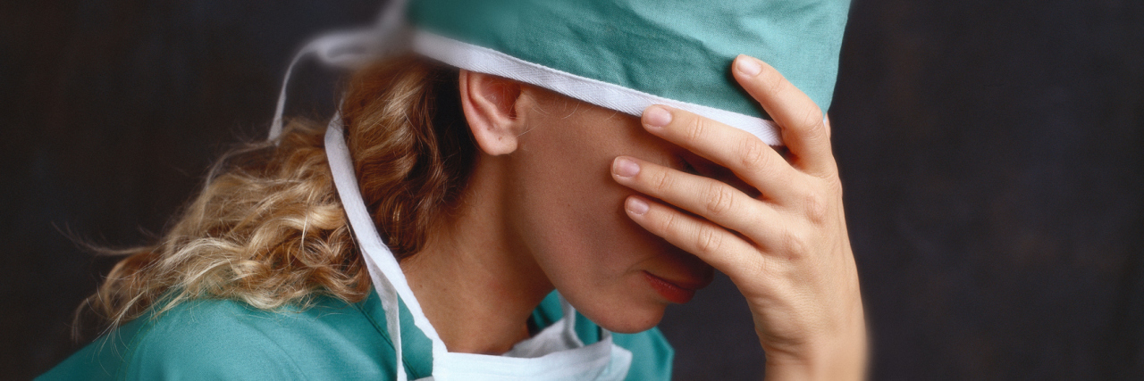 A female medical professional wearing scrubs, with her head in her hand, in front of a dark background.