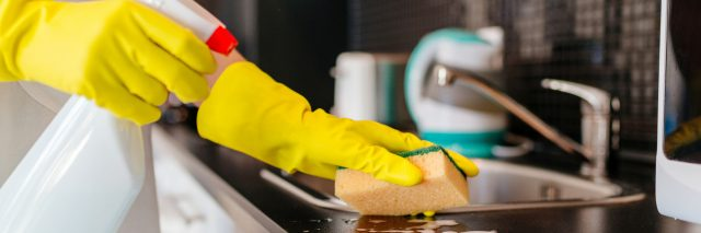 A woman cleaning a kitchen counter with a spray bottle and sponge.