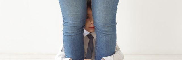 Boy hiding behind mom's legs