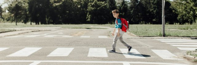 Boy at school crossing with backpack