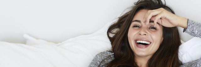 A woman laying on a bed with white sheets, holding a cup of coffee, while laughing.