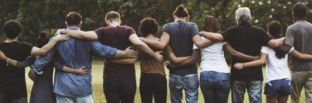 A group of friends huddled together, facing away from the camera.