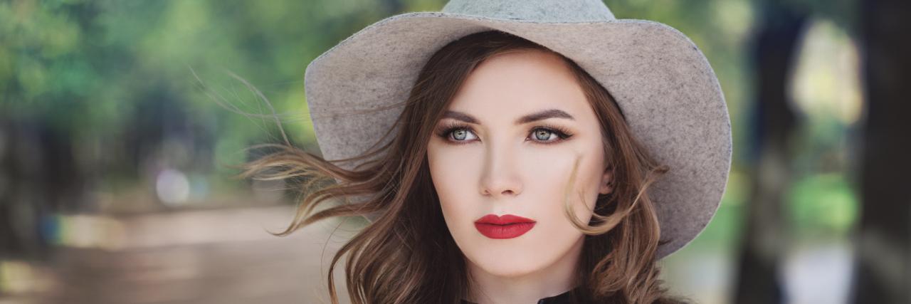 A woman outside, wearing a sun hat.
