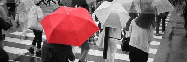 A red umbrella in a crowd of people crossing the street.