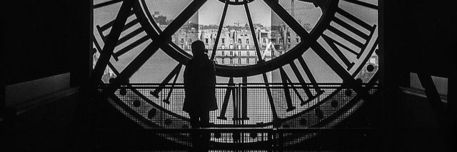 A woman standing inside a tower, in front of a giant clock.