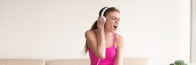 Woman wearing headphones listening music, dancing and emotionally singing song at home.