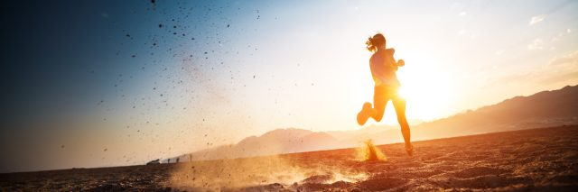 A picture of a woman running in a sandy desert as the sun is setting.