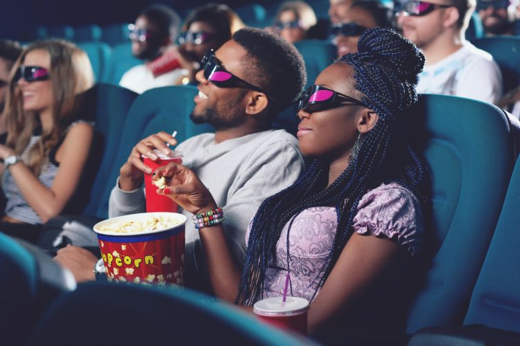 Side view of boyfriend and girlfriend wearing 3d glasses watching movie and spending time together. Couple of africans in modern cinema hall eating popcorn, drinking cola and looking at projector.