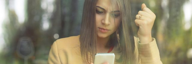 A woman holding her phone, clenching her fist