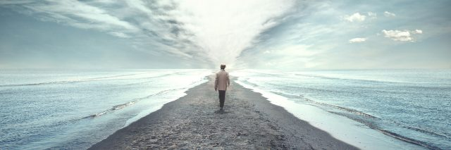 A man walking on a pathway between two seas.
