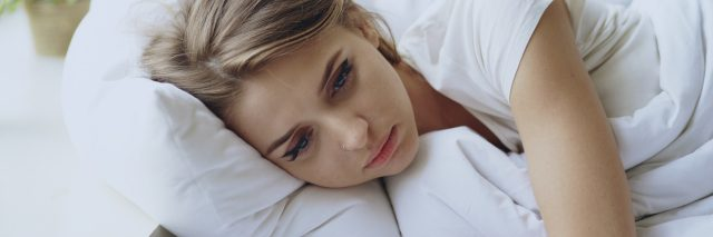 Depressed young woman lying in bed and feeeling upset after quarrel with her boylfriend in bedroom at home