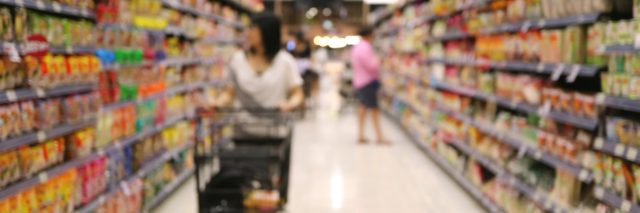 A blurry image of a woman pushing a shopping cart in a grocery store.