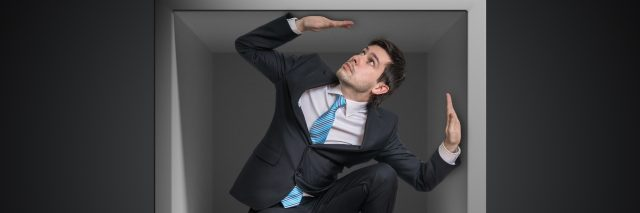 Businessman trapped inside uncomfortable small box.