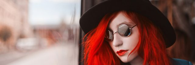 A woman with red hair look out a window.