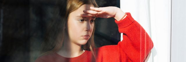 A young girl wearing a big sweater looking out a window