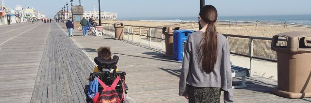 Mother walking side by side with son who is using motorized wheelchair as they go down a wooden walkway.