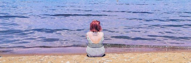 A picture of the writer sitting in front of a body of water.