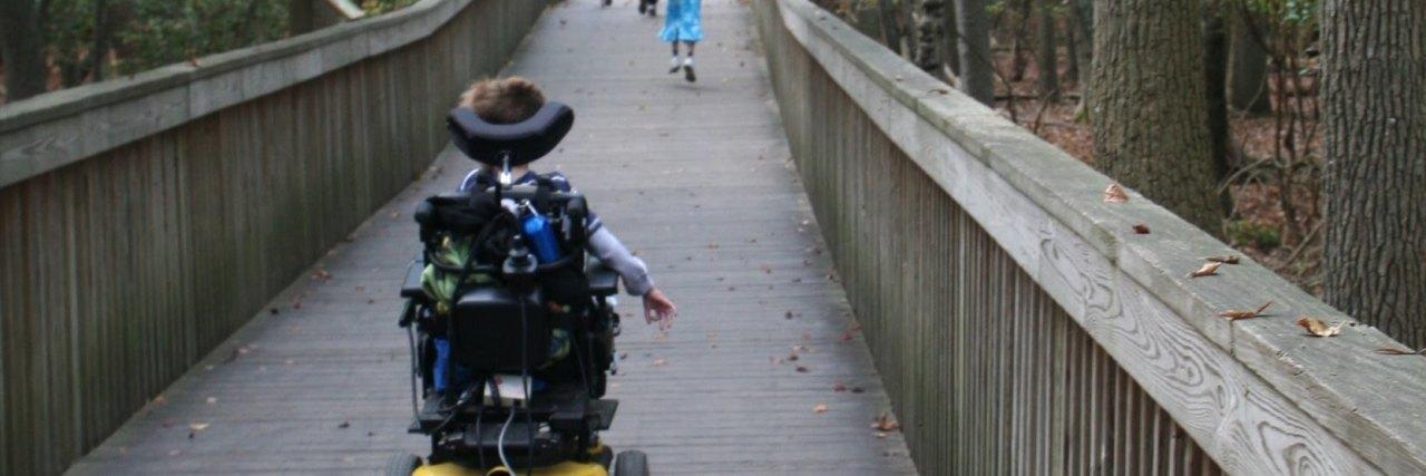 Child in wheelchair crossing a bridge behind siblings