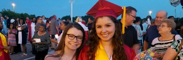 A picture of the writer wearing a red graduation gown, standing next to her friend.