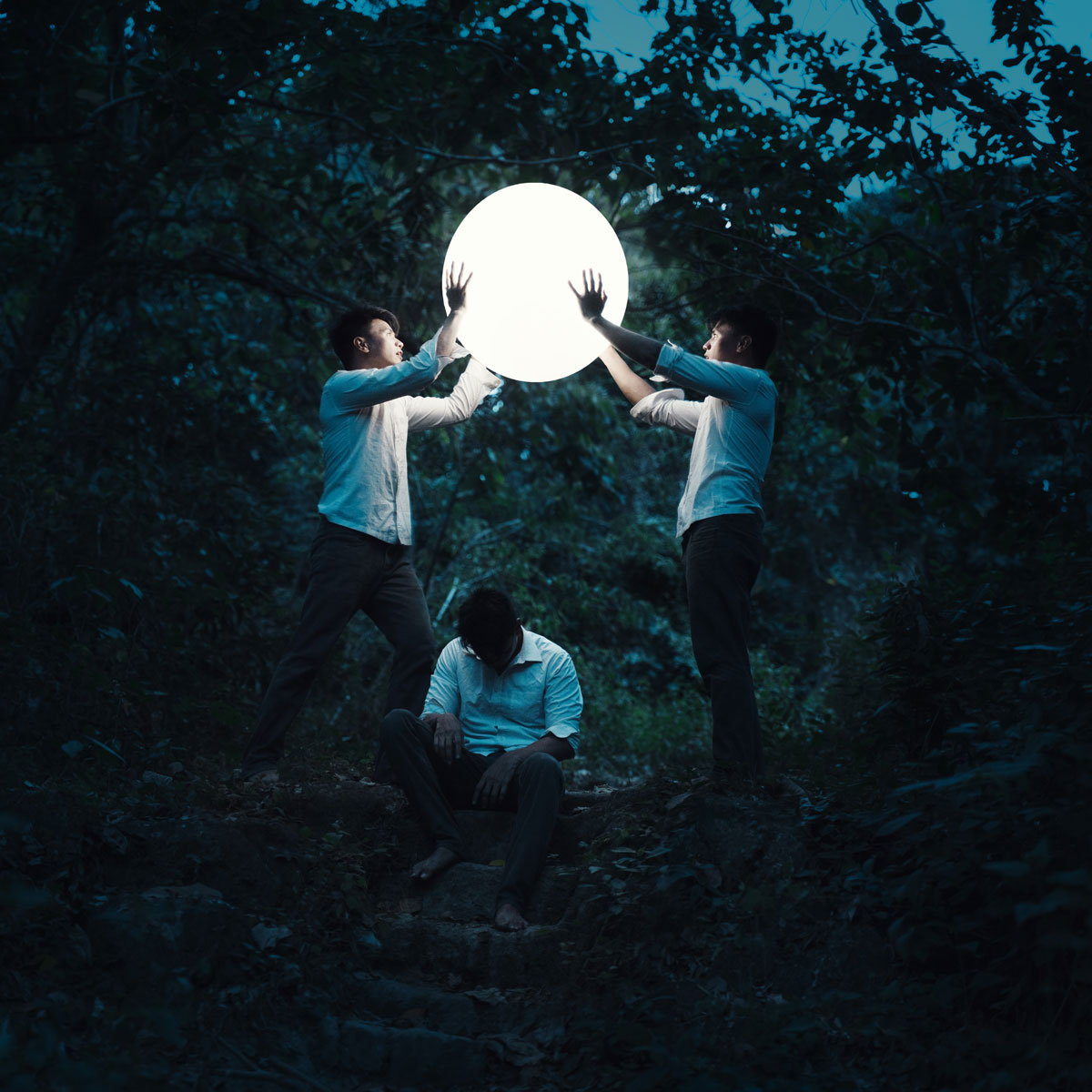 Mike Alegado concept photography image of men holding large white ball above third depressed man