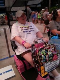 A picture of the writer in her mobility scooter at the theme park.