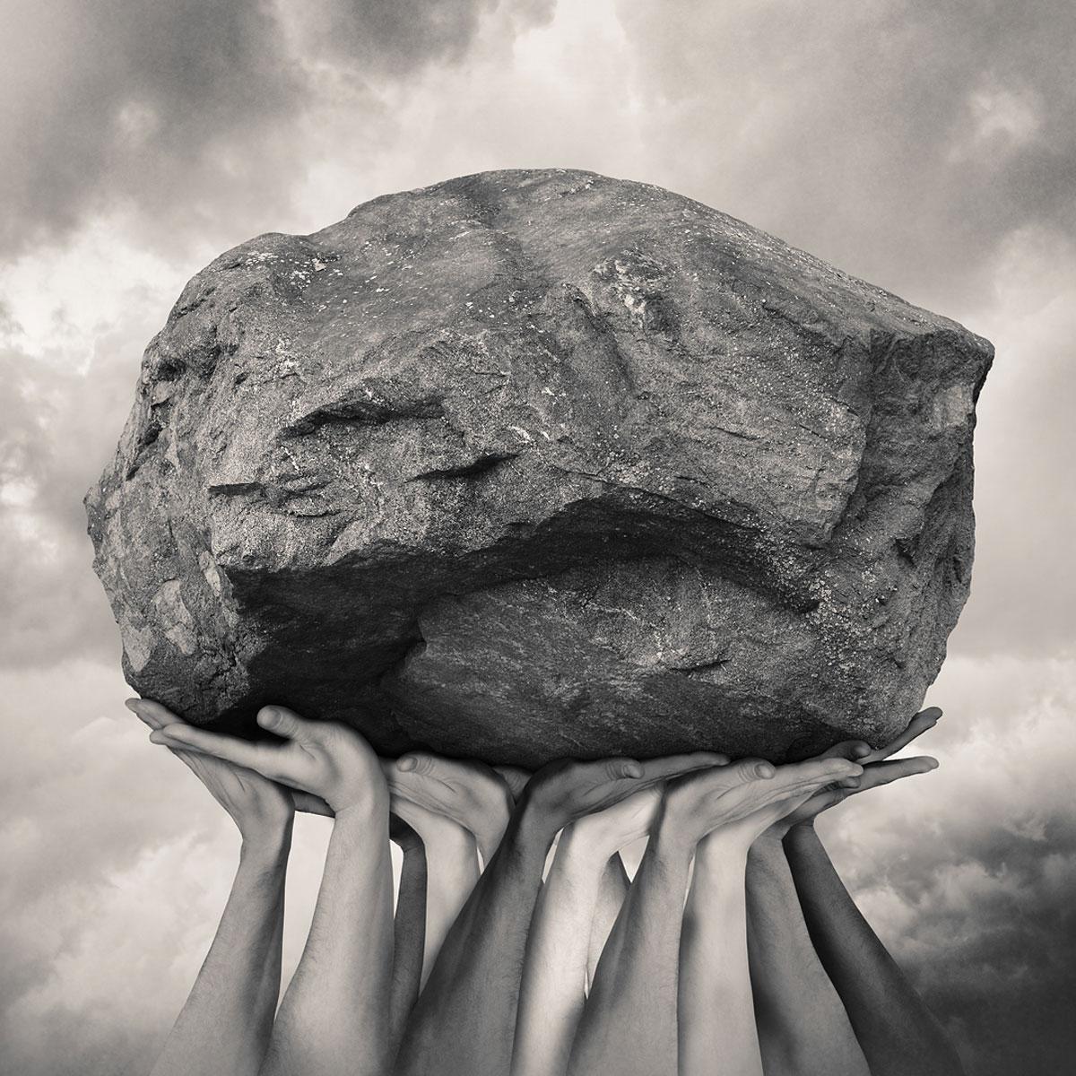 Tommy Ingberg image of hands holding up large stone
