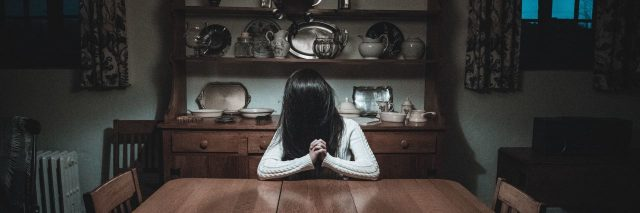 woman sitting at table in dark room with hair hiding face