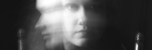 long exposure black and white photo of young woman turning head