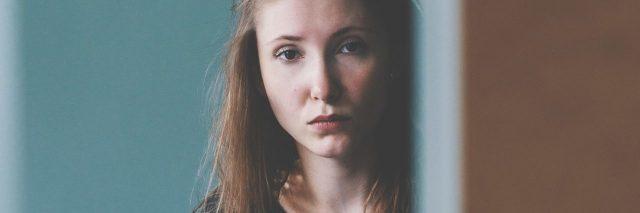 woman looking upset partially hidden by frame of door