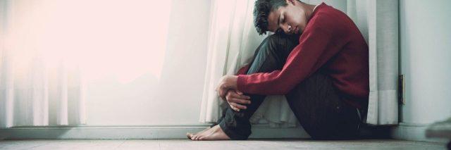young man sitting on floor under window hugging knees