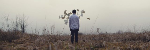 man facing away from camera in field having thrown pages into air