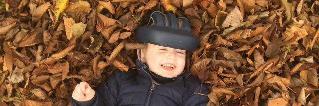 Little boy wearing a medical helmet smiling and laying on a pile of leaves