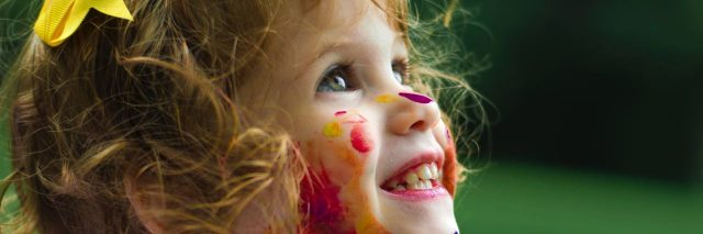 Little girl covered in colorful pain all over face, nech, white clothes. She is smiling off to the side