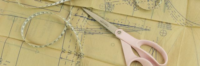 Clothing pattern, scissors and measuring tape.