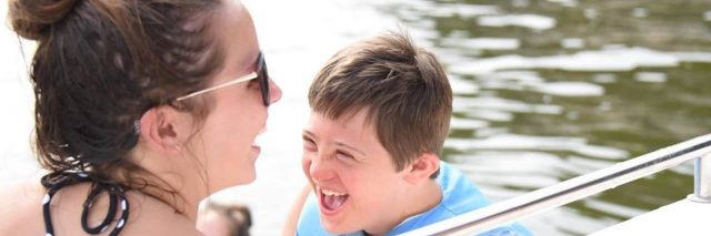 Sister and brother smiling looking at each other in a boat