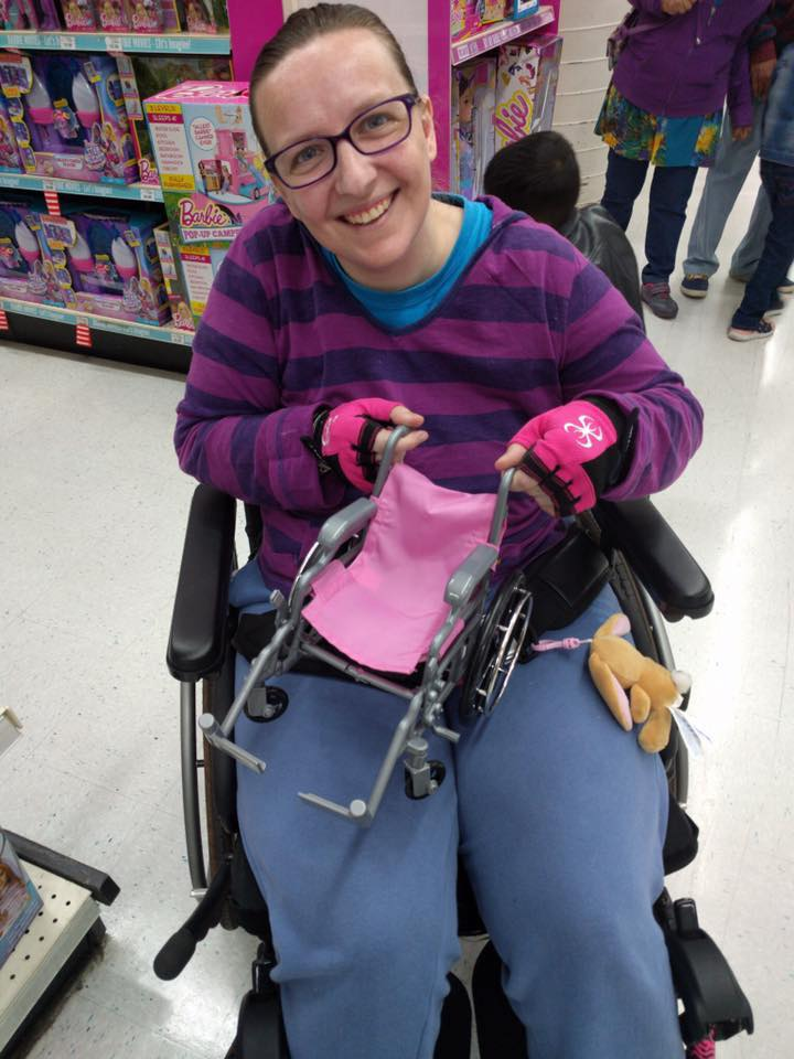 woman out shopping in her wheelchair holding a tiny toy wheelchair