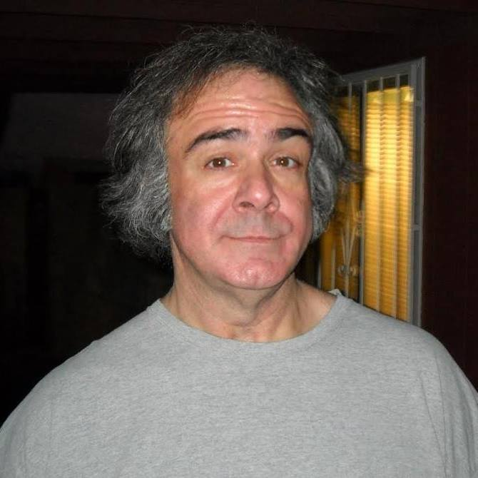 man in a gray shirt smiling