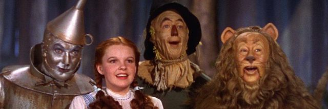 "A picture from ""The Wizard of Oz,"" showing the Cowardly Lion, Tin Man, Dorothy, and the Scarecrow."