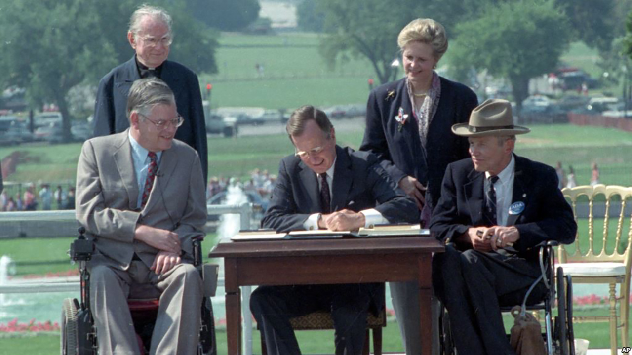 President George Bush signs the ADA as Justin Dart and other distability rights leaders look on.