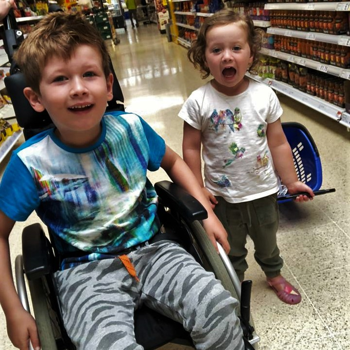 Picture of two kids, boy in a wheelchair and little sister next to him walking and opening her mouth wide