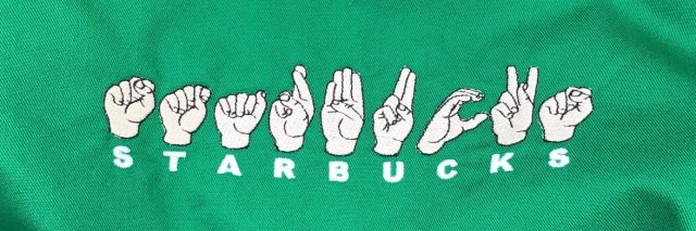 "Starbucks apron with the word ""Starbucks"" in fingerspelling."