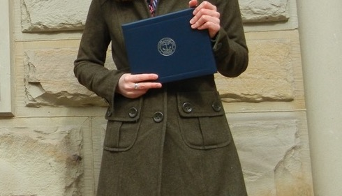 author holding her degree in her hand