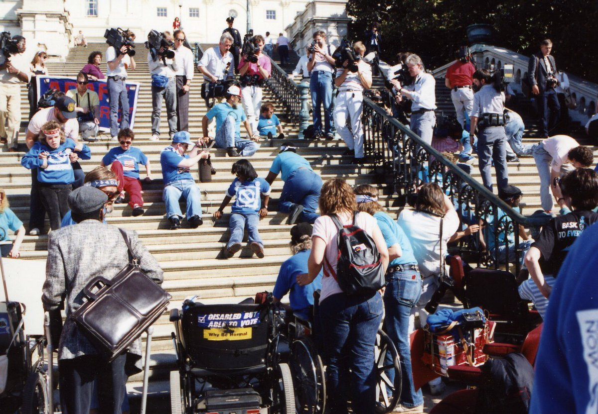Disability rights activists crawl up the Capitol steps to demand passage of the ADA.