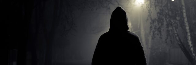 A person walking in the night, wearing a dark hoodie.