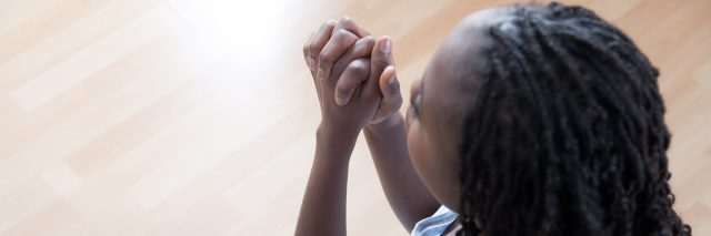 A woman on her knees with her hands folded as she prays.