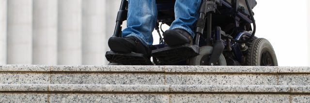 Wheelchair user in front of staircase.