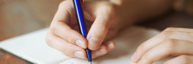 a person's hands writing in a diary