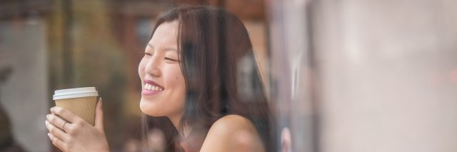 young chinese woman sitting next to windows in cafe.