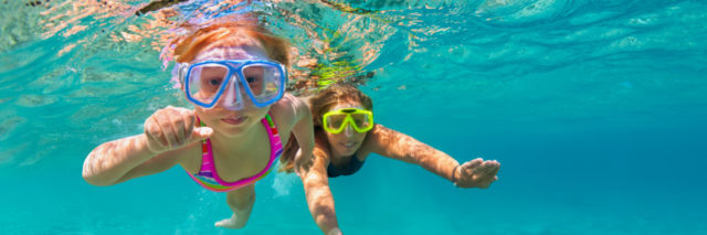 Two girls swim underwater with goggles looking at camera